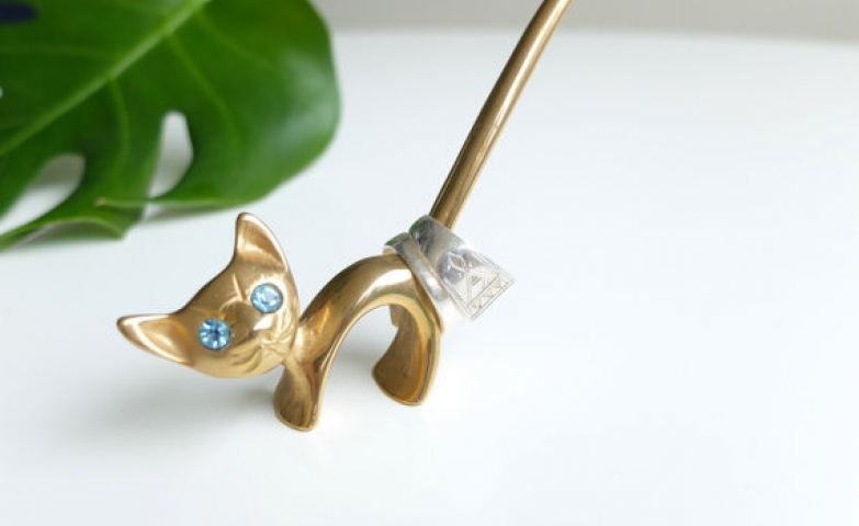 1960's style cat ring holder made from metal, with gold finish and blue gem eyes, great for jewelry display.