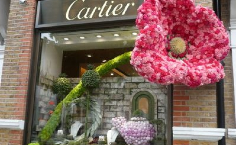 Cartier really know how to get peoples attention, for this storefront they used a giant flower with bright green and pink colors. Also the display is like taken from a fairy tale.