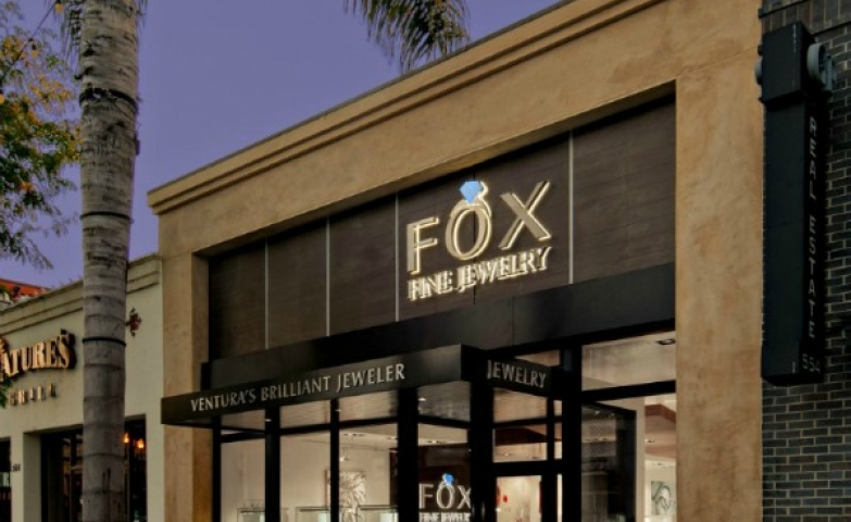 Fox Fine Jewelry's store front shows a bright gold logo, with glass window displays and brown exterior, allowing a lot of the interior to be exposed and observable from the outside.
