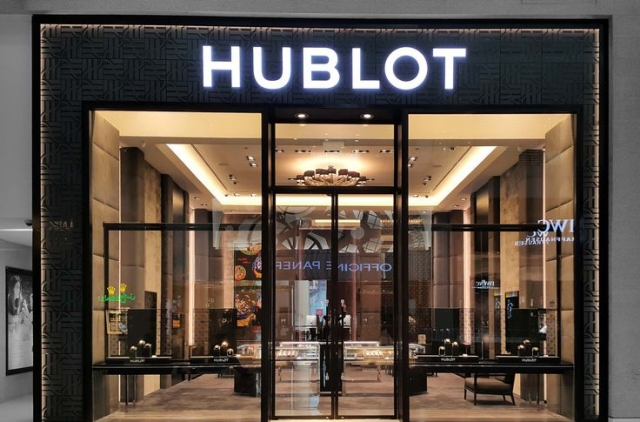 Hublot storefront with tall glass windows, simple discrete black displays and a bright logo. Also shows a lot from the interior, giving an inviting feeling.