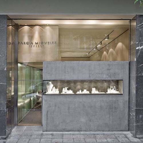 Geometrical architecture, marble finish and uneven glass windows with a small glass rectangle display. A nice inspiration idea for a jewelry shop design.