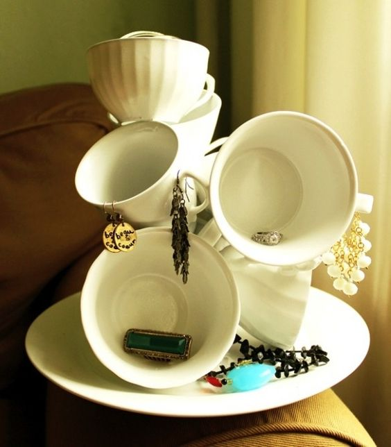 Different sized cups put together on a plate, a fun and creative way for jewelry displays.