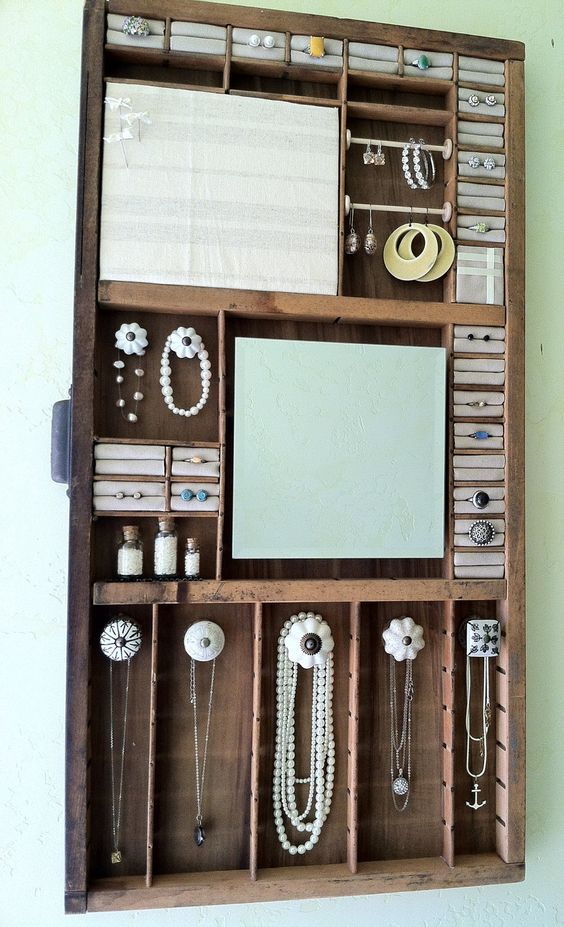 This jewelry organizer is made from a wood antique printing tray and it looks stunning for keeping and hanging your favorite pieces.