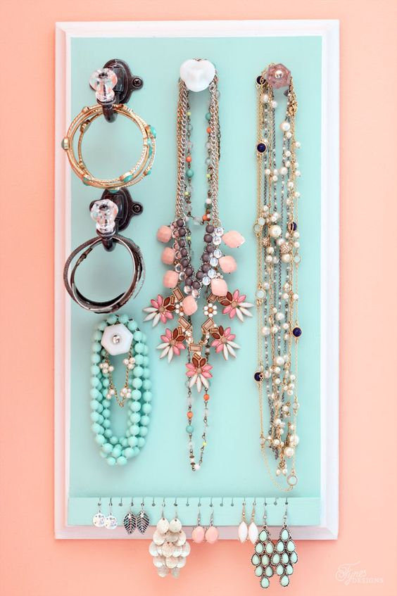 Baby blue jewelry organizer for wall placement, with different hangers for necklaces, bracelets and earrings.