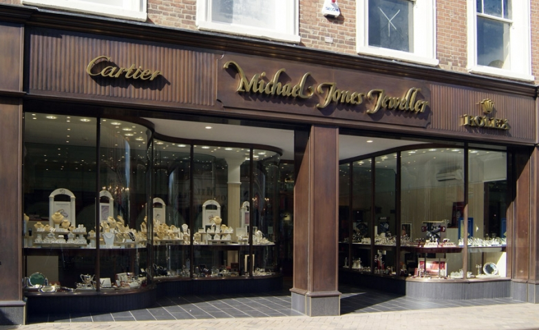 Massive looking entrance for Michael Jones Jeweller with brown pillars and gold lettering, followed by a wide glass display