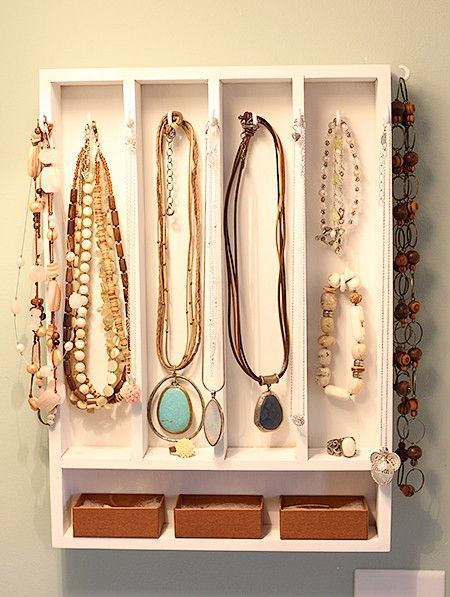 Small discrete white wall jewelry organizer, with hangers for necklaces, bracelets, and small boxes for earrings and rings.