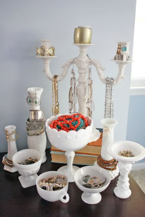A creative idea for a jewelry organizer is using some household objects like the candle holder for hanging necklaces, and teacups for holding various jewelry.