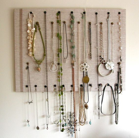 This jewelry organizer is an easy DIY idea, by using a board with a cloth over it and some hanging pins. Ideal for necklaces.