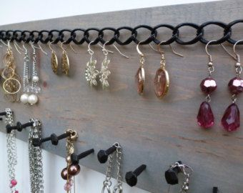Jewelry storage idea, necklace and earring holder organizer as a wall display. It consists of a mounted rack made from reclaimed wood and rustic nails in walnut finish.