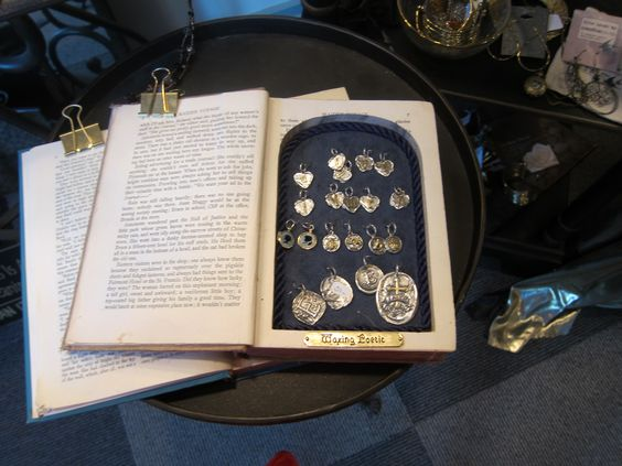 Vintage ideas for jewelry store display, medallions placed inside an old book, which has its pages cut out.