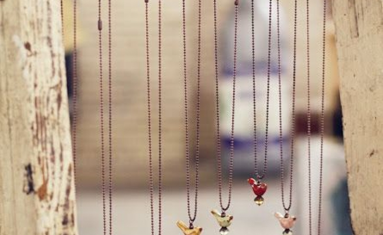 Cute bird necklaces displayed on rungs of an old timber ladder, a nice way to show off merchandise for an outdoors exposition.