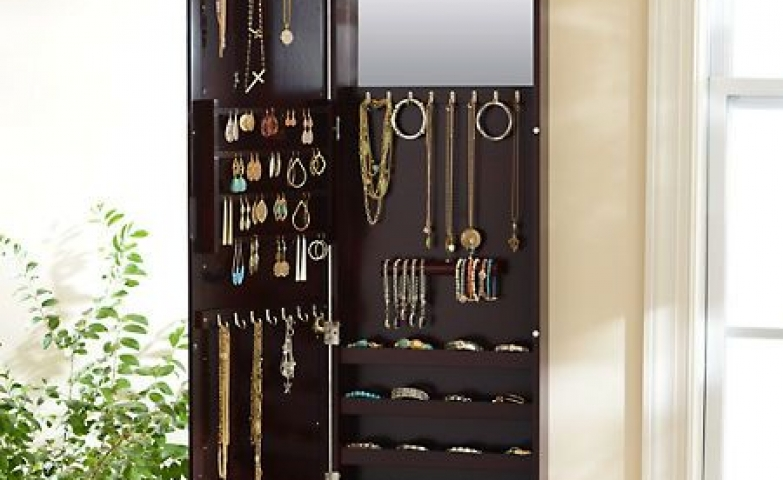 A mahogany wood jewelry armoire, which can be casually placed over the door and has plenty of storage space and even a classy mirror inside.