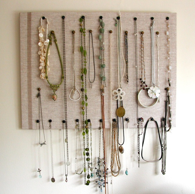 Use solid fabric like linen atop your cork and black hangers to organize your necklaces.
