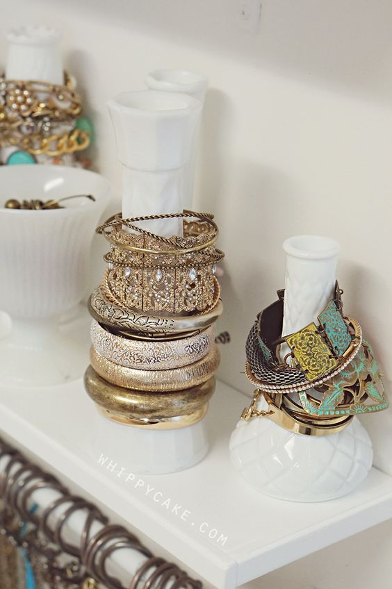 A great idea to organize your bracelets by sliding them over bottles and vases