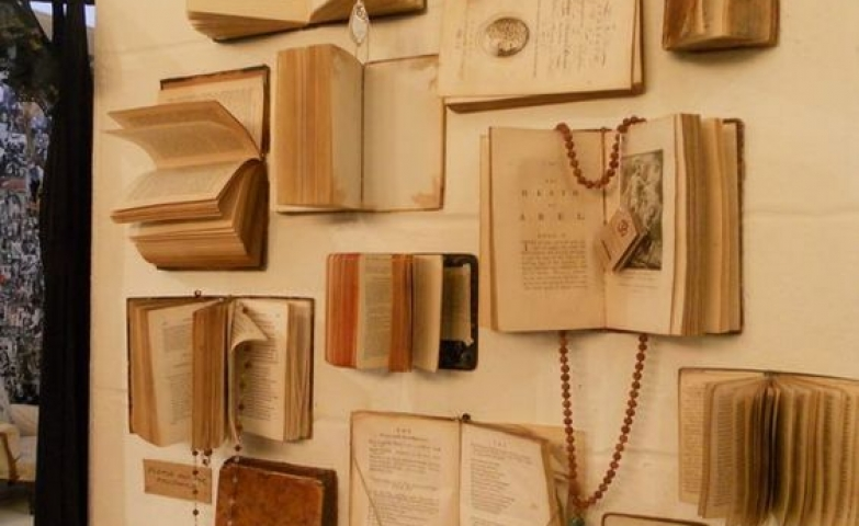 Projects made with different sized old books placed on the wall and used to hang necklaces.