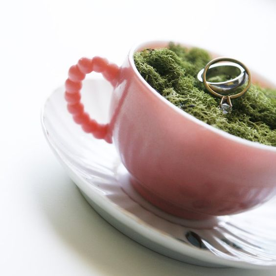 A creative way to display your rings with this pink teacup and musk-like green fibers