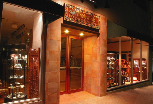 Storefront of Tradewinds, lots of orange combined with black and the popular tall glass windows for the exterior look.