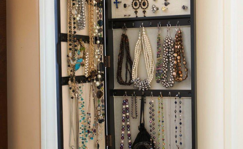 Another design for an over the door storage solution, a mirrored jewelry armoire in black color with hangers for necklaces and bracelets.