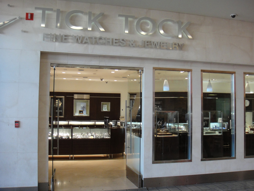 White marble walls, rectangle glass windows and all glass doors. This is the store front of Tick Tock Watches.