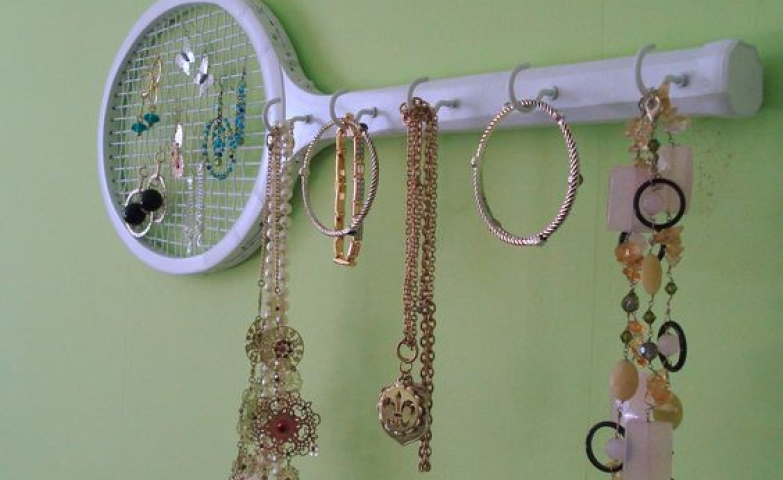 A vintage retro wooden tennis racket painted all white and with hooks installed on it, can be now used as a jewelry storage and holder.