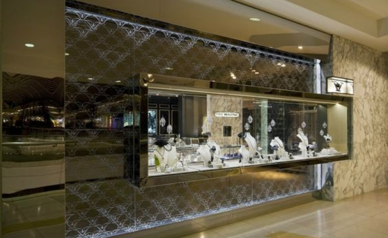 A wide glass rectangle display for the merchandise standing out of the front of the Trewarne Fine Jewelry Store in Chadstone.