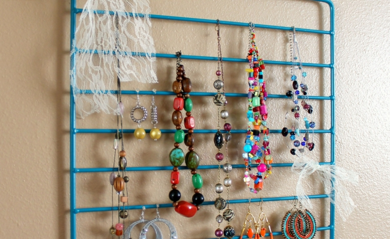 This small jewelry holder is a great DIY idea which you can make with a blue metal frame and sheer white ribbon. Here they used it for colorful stone necklaces and awesome earrings placed on a cream painted wall.
