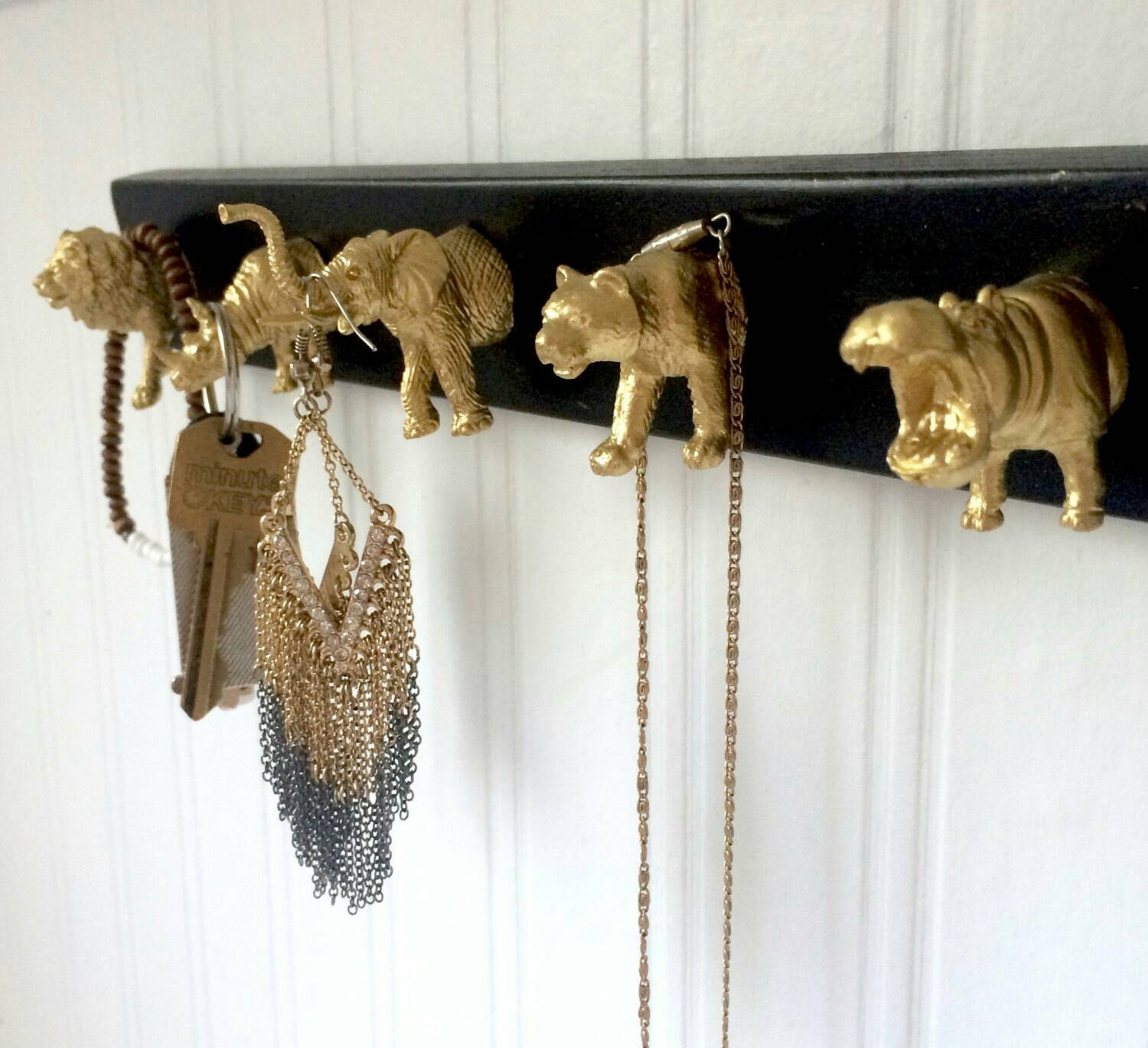 Take a black wooden rectangle and some gold animal head hooks, and you've got a wall hanging jewelry organizer.