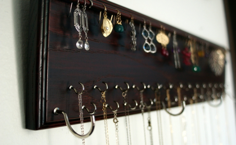 A great jewelry organizer by Bellezamia is this wall mounted jewelry hanger with a mahogany wood finish, for earrings and necklaces.