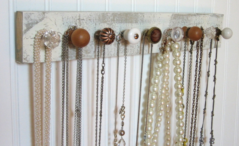 So many DIY wall mounted jewelry organizer ideas come from a simple wooden rectangle with a few vintage knobs placed on with, great for hanging necklaces.