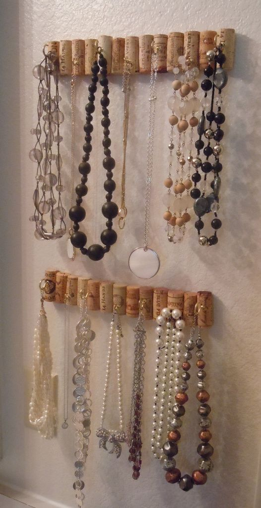 Another fun way to build a necklace organizer from wine cork is to glue them together, place a few small hooks and then just install on the wall.