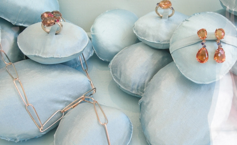 Baby blue silk covered cushions used as a creative jewelry display and visual merchandising.