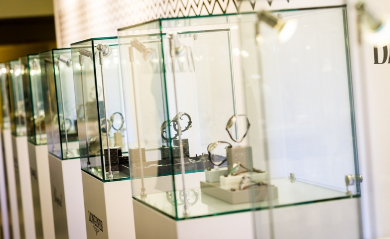 Watches displayed inside glass boxes on white stands with the name of the brand on them.