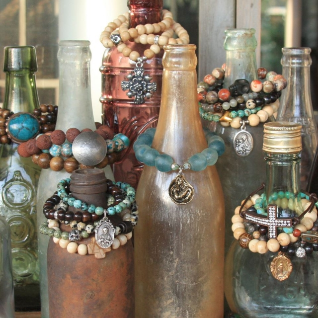 Why not recycle some old bottles and use them for bracelets displays as a vintage visual setting.