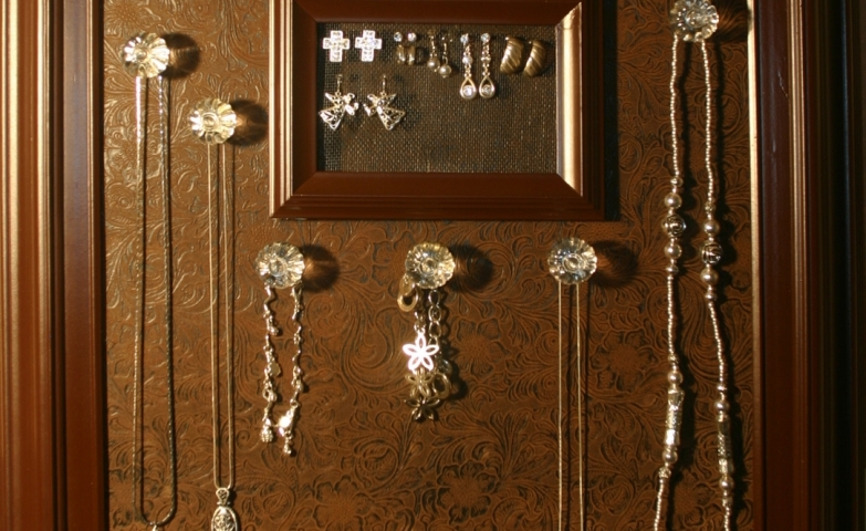 A jewelry display which can be easily made using a brown frame, brown board and a few transparent knobs.