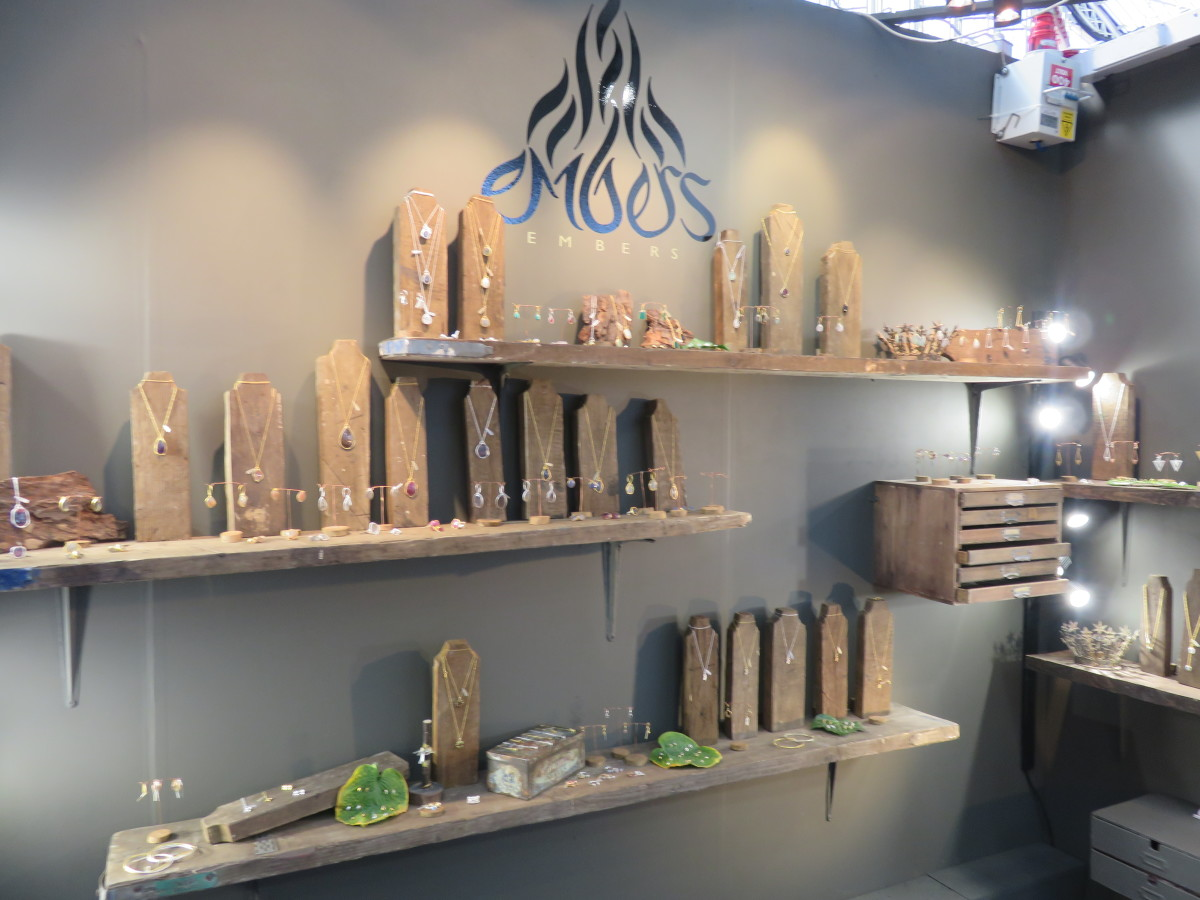 Natural looking setting with wooden necklace holders and other nature inspired decoration for a jewelry store interior visual merchandising. Interesting stands to display jewelry.