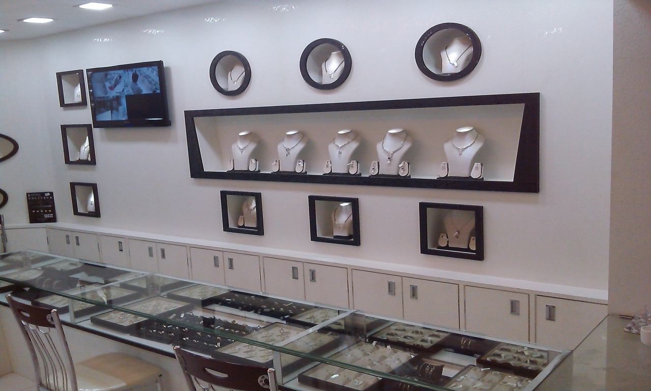 A jewellery shop interior with glass displays and built-in stands of different shapes used to display necklaces, inspiration and ideas for jewelry display.