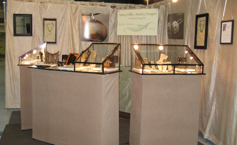 Simple display ideas from this jewelry booth, using three main glass box displays with interior lighting.