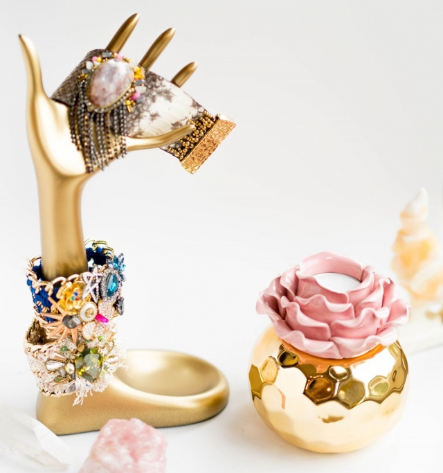 Gold holder in the shape of a hand and small gold vase with a rose shaped decorative piece inside it for DIY jewelry display ideas.