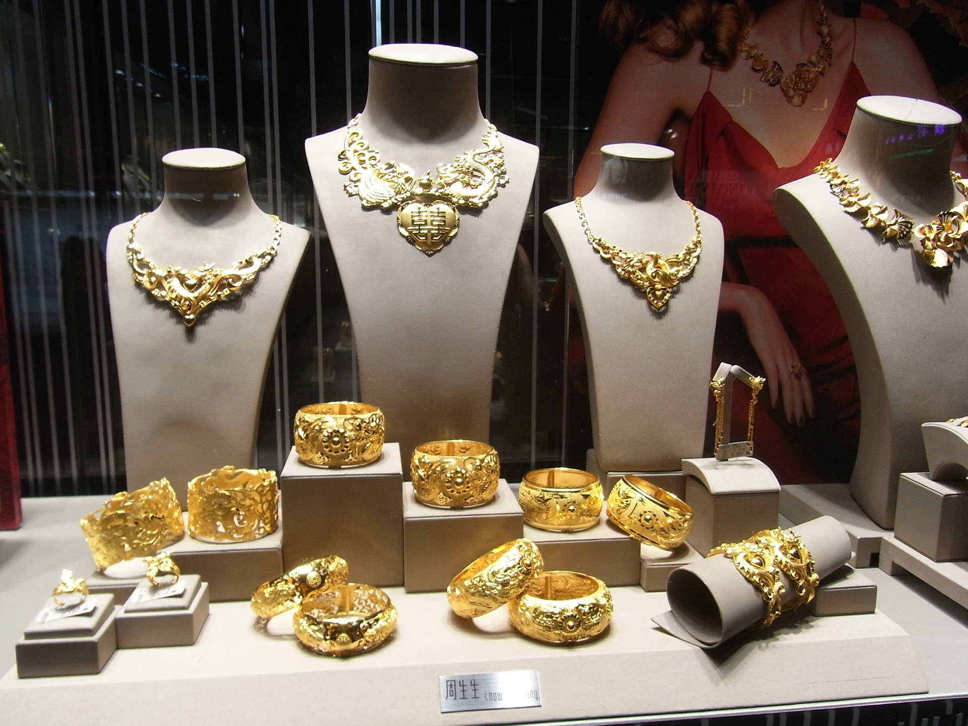 Fashionable jewelry window display focused mostly on the over-sized gold bangles. A simple display which puts the attention on the jewels rather than the decoration.