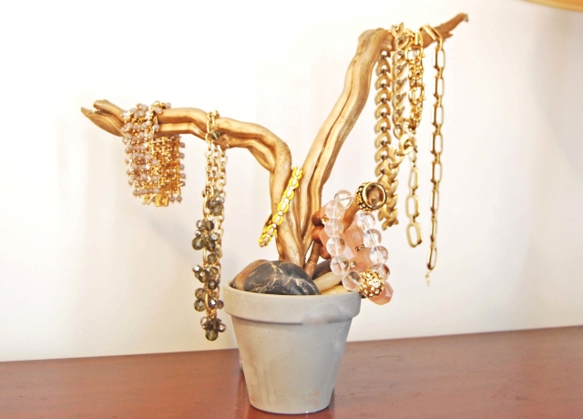 A grey flower pot filled with large stones and gold painted branches, inspiration for fun ways to hang your jewelry.