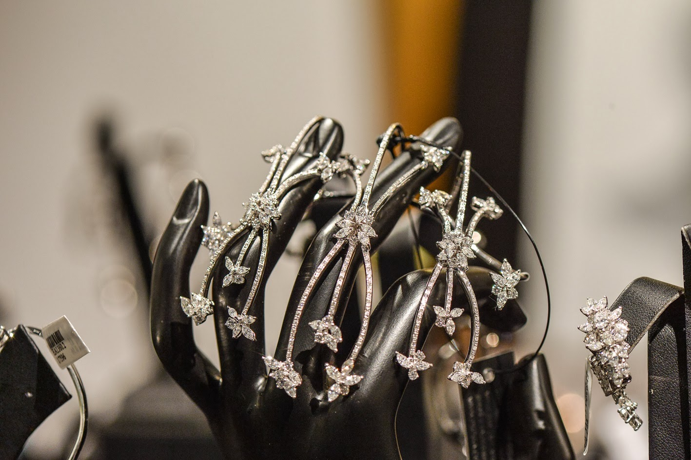Exquisite designer pieces seen up-close on a black display hand, beautiful ideas for jewelry display.