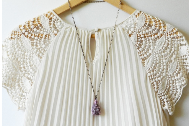 Combination for funky jewelry displays by hanging a necklace alongside a matching, delicate white blouse.