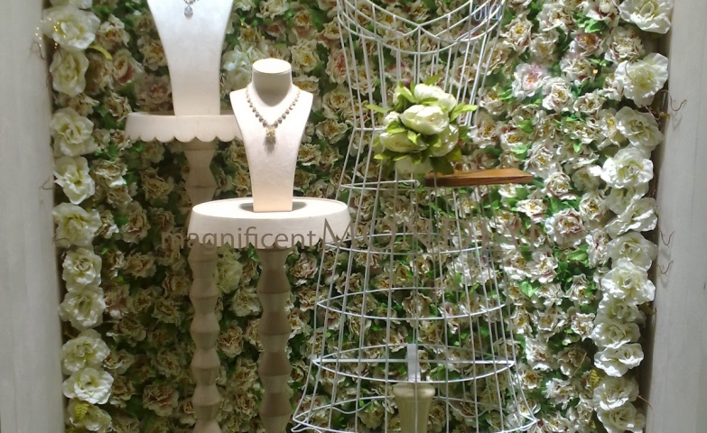 A wall of flowers and delicate busts for necklace display, a really feminine touch for jewelry display ideas.