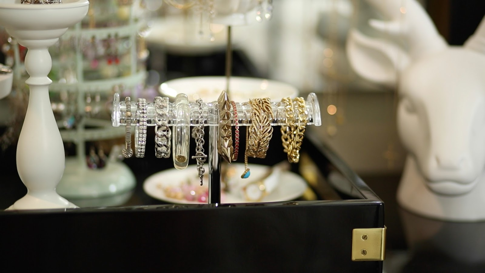 Close-up on a bracelet rack with gold and silver jewelry on display.