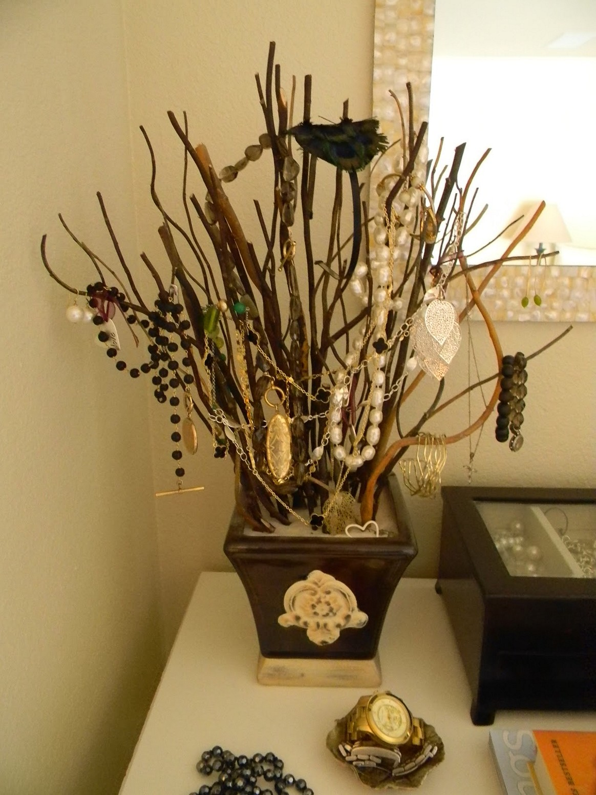 Jewelry display ideas for your home by placing various branches in a pot and hanging your jewels on them.