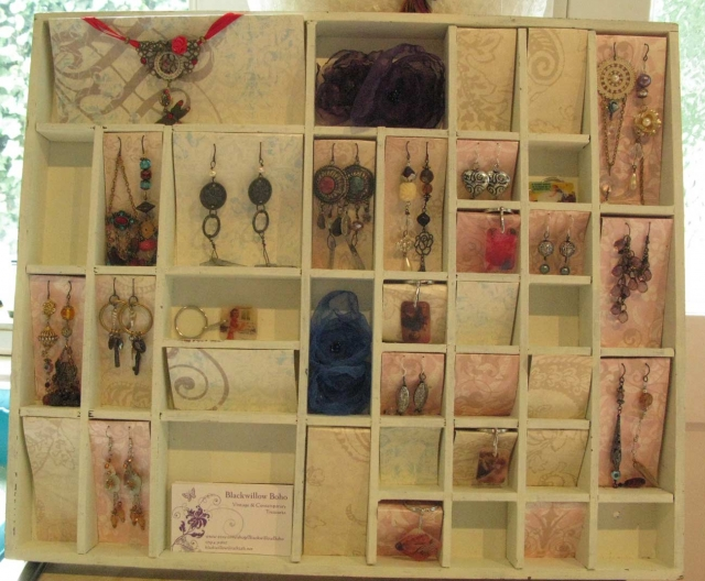 Great jewellery display case idea made from a wooden organizer with different sized boxes and funky colored carton used for hanging different jewels.