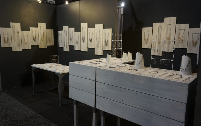 Jewelry booth display with white furniture displays and white boards for necklace display.
