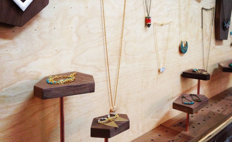 Jewelry display ideas for stores, a wooden wall to which you can attach all sorts of stands and holders for your jewelry.
