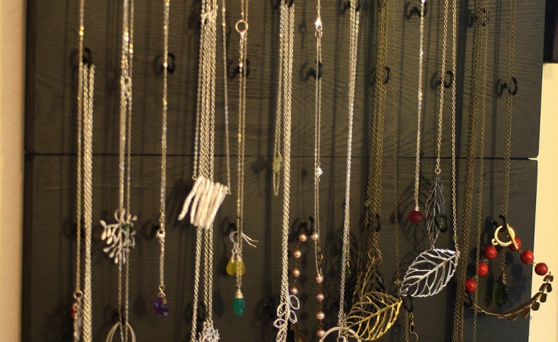 Black wall mounted jewelry organizer with hooks for necklace hanging and racks for earrings.