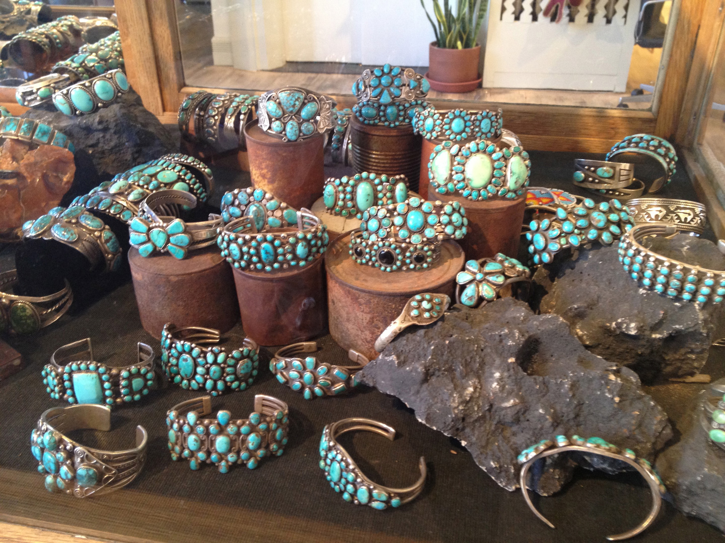 Old rusty cans and grey rocks to create a jewelry display setting for silver and turquoise stone jewelry pieces.